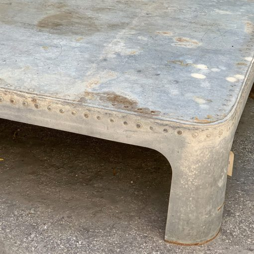 Antique galvanized metal coffee table, top right corner